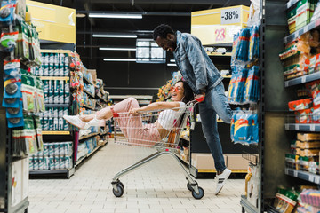 Happy couple playing with shopping cart in supermarket