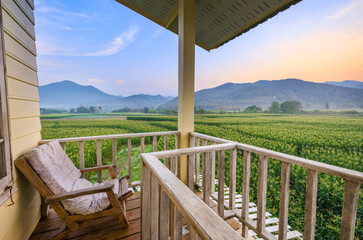 Balcony home exterior with chairs and decoration in contemporary home. Morning corn field scene at sunrise.