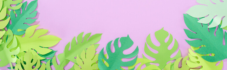 top view of green paper cut tropical leaves on violet background with copy space, panoramic shot Wall mural