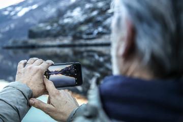 homme mature prenant une photo des fjords de Norvège