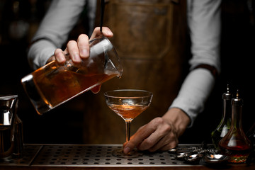Bartender pours the alcohol cocktail from strainer