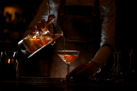Bartender pouring the alcohol cocktail with strainer