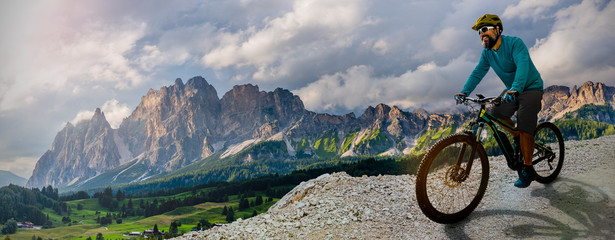 Man cycling on electric bike, rides mountain trail.  Man riding on bike in Dolomites mountains landscape. Cycling e-mtb enduro trail track. Outdoor sport activity. Fototapete