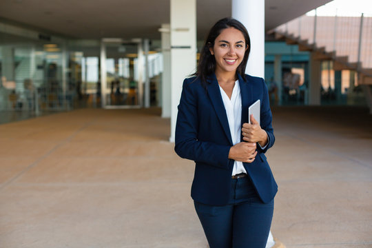 Cheerful businesswoman with digital tablet. Beautiful happy young woman holding tablet pc and smiling at camera in office building. Technology concept