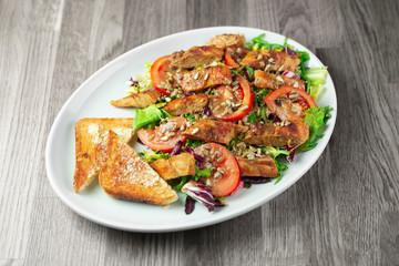 Fototapeta Sałatka z piersią z kurczaka wraz z grzankami, pomidorami oraz słonecznikiem  obraz