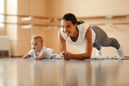 Happy mother with a baby doing plank exercise in health club.
