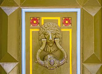 Old metal doorknob in the shape of lion head on old wooden door
