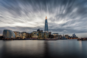 Fotomurales - Die markante Skyline von London an der Themse mit den beleuchteten Wolkenkratzern am Abend mit Wolken, Großbritannien