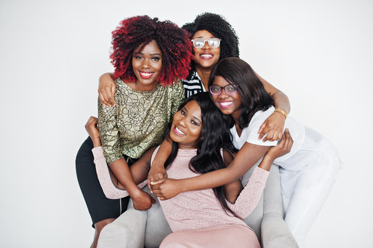 Happy brightful positive moments of four african girls. Having fun and smiling on chair against white empty wall. Lovely moments of four hugging best friends.