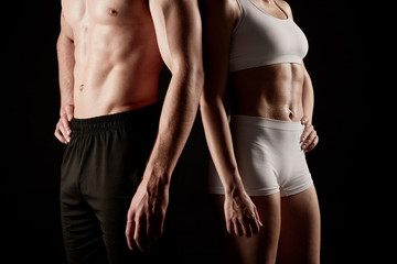 Fit couple in sportswear poses at the camera standing close together in a close-up.