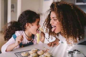 mother and daughter laughing while decorating baked cookies