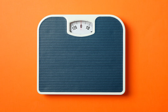 Blue weigh scales on orange background, top view