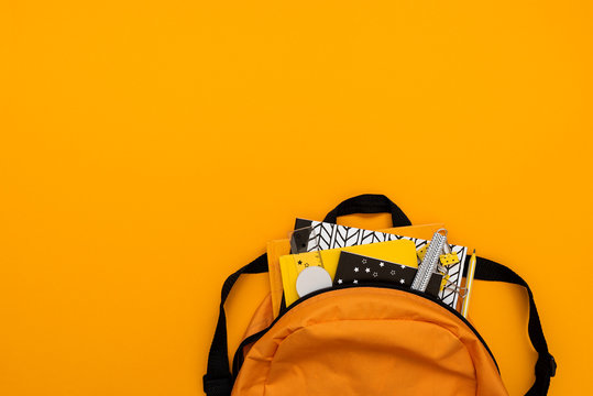 Back to school concept. Backpack with school supplies on yellow background. Top view. Copy space. Flat lay