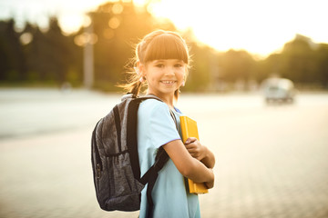 Happy little student girl with a backpack on her way to school.