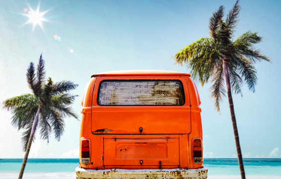 A red orange vintage van in the ocean and sunny beach view. Summer time and fun on the beach.