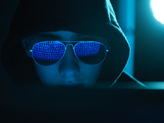 Cyber Crime, reflection in spectacles of virus hacking a computer, close up of face
