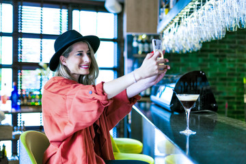 Smiling woman sitting at the counter of a bar taking a selfie