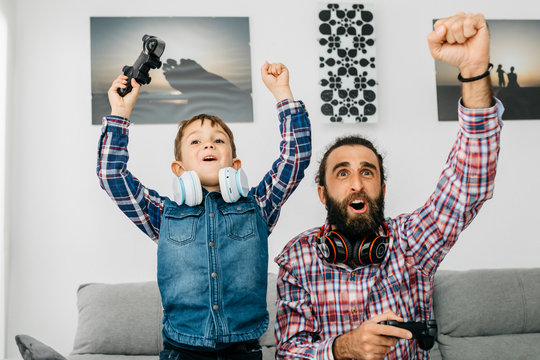 Father and son playing computer game at home