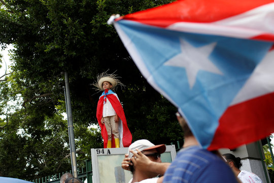 A kid wearing a Puerto Rican flag attends a rally to celebrate the resignation of Puerto Rican Governor Ricardo Rossello in San Juan