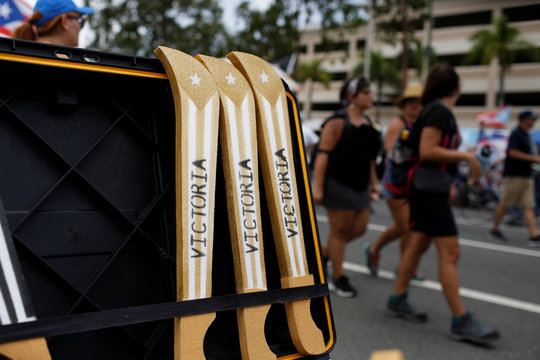 """Foam machetes painted with the Puerto Rican flag and the writing """"Victory"""" are seen for sale during a rally to celebrate the resignation of Puerto Rican Governor Ricardo Rossello, in San Juan"""