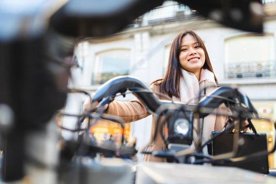 Spain, Madrid, smiling young woman using rental bike in the city