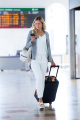 Young businesswoman texting with her mobile phone while walking with suitcase on the hall of the train station