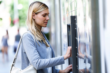 Young businesswoman using a credit card to withdraw money on a cash machine outdoors