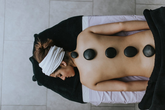 Young woman with heated stones on her back
