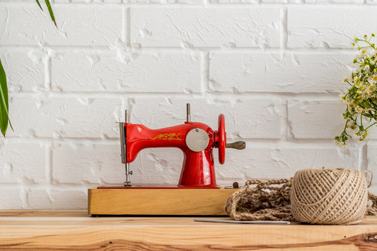 Red sewing machine on a wooden table. Sewing industry. Diy