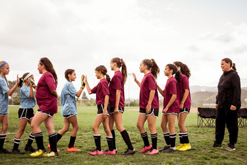 Female coach looking at girls high-fiving while walking on soccer field against sky during competition
