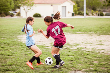 Full length of girls in sports uniform playing soccer on field during competition