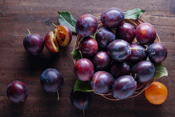 Ripe juicy plums on a wooden background.