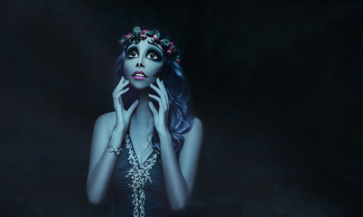 Creative Work Makeup Artist. Cartoon image for the holiday to the Halloween party. Sugar skull with big eyes. Blue hair and skin. Decoration wreath of withered dry roses. Black background