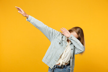Portrait of cheerful blonde young woman in denim casual clothes showing dab dance gesture isolated on bright yellow orange wall background in studio. People lifestyle concept. Mock up copy space.