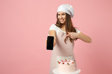 Chef cook confectioner or baker in apron white t-shirt, toque chefs hat cooking cake or cupcake at table hold cellphone isolated on pink pastel background in studio. Mock up copy space food concept.
