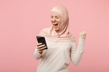 Arabian muslim woman in hijab light clothes posing isolated on pink background. People religious Islam lifestyle concept. Mock up copy space. Using cellphone, typing sms message, doing winner gesture.