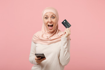 Surprised young arabian muslim woman in hijab light clothes posing isolated on pink background. People religious Islam lifestyle concept. Mock up copy space. Using mobile phone, hold credit bank card.