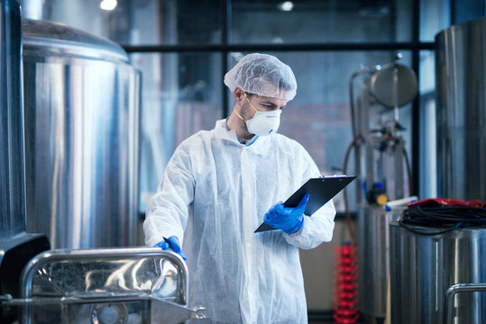 Technologist working in food processing factory checking quality and production. Industrial worker in white protective clothes holding checklist and reading results.