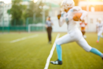 Photo of young athlete playing American football running on green field on summer