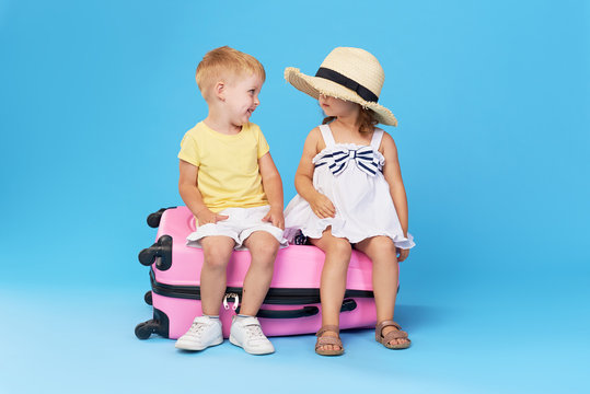 Happy kids sitting on colorful pink suitcase prepared for summer vacation. Young travelers. Little girl and boy, sister and brother, having fun isolated on blue background