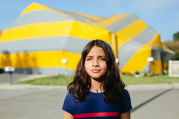 Portrait of a girl outside with a tented house in the background