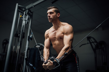 Young man doing chest exercise with cross machine-Edit