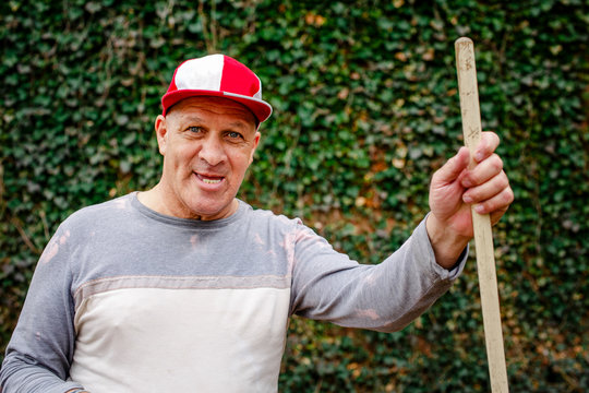 Portrait of a senior man in a ball cap with toothy grin doing yardwork