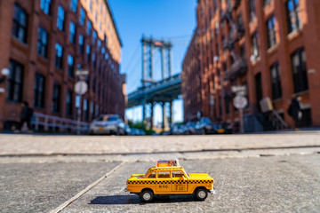 Fotomurales - Vintage old Taxi toy in New York City most popular places. Classic Yellow Cab in Manhattan and Brooklyn. The symbol of New York. Driving a taxi through Brooklyn.