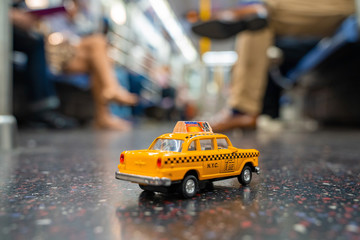 Vintage old Taxi toy in New York City most popular places. Classic Yellow Cab in Manhattan and Brooklyn. The symbol of New York. Driving a taxi on a subway.