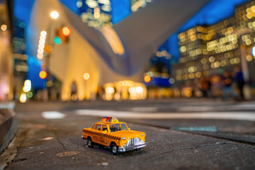 Wall Mural - Vintage old Taxi toy in New York City most popular places. Classic Yellow Cab in Manhattan and Brooklyn. The symbol of New York. Driving a taxi through Manhattan island.