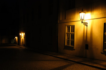 Old lanterns illuminating a dark alleyway medieval street at night in Prague, Czech Republic. Low key photo with brown yellow tones from the lanterns as single light sources against the dark shadows Fotomurales
