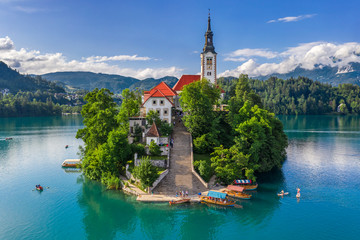 Bled, Slovenia - Aerial view of beautiful Pilgrimage Church of the Assumption of Maria on a small island at Lake Bled (Blejsko Jezero) and lots of Pletna boats on the lake at summer time with blue sky