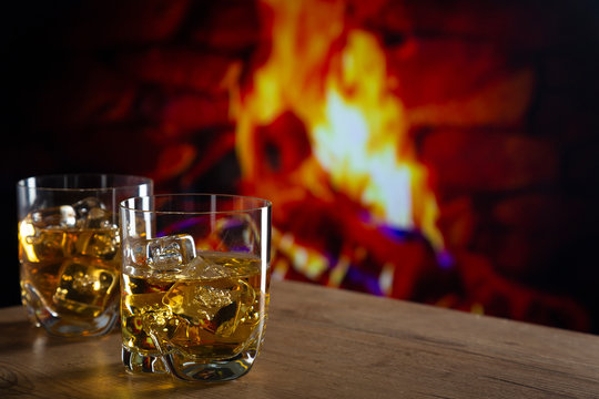 Glass of whiskey in front of a fireplace