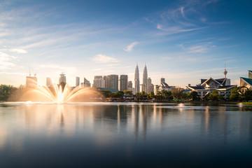 Photo Stands Kuala Lumpur Kuala Lumpur city skyscraper and fountation with nice sky morning at Titiwangsa Park in Kuala Lumpur. Malaysia. Travel and Vacation concept.